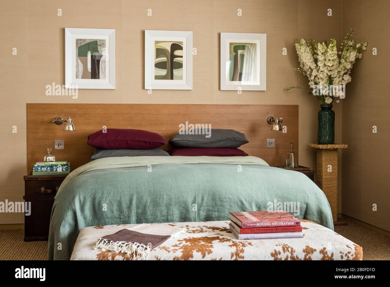 L'art moderne au-dessus d'un lit dopuble avec une couverture vert clair et des livres sur un tabouret de cowhide. Banque D'Images