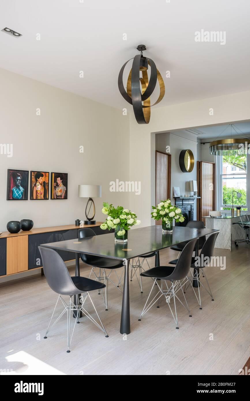 Suspension classique dans des sections de laiton et de bronze au-dessus de la table à manger en chêne coloré ébène sur des pieds en bronze avec le plateau latéral Molteni Banque D'Images