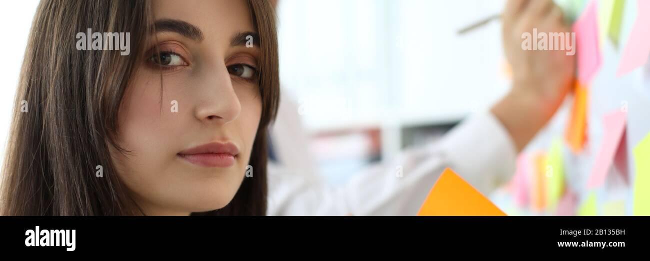 Pretty female office worker holding papier collant à la caméra en Banque D'Images