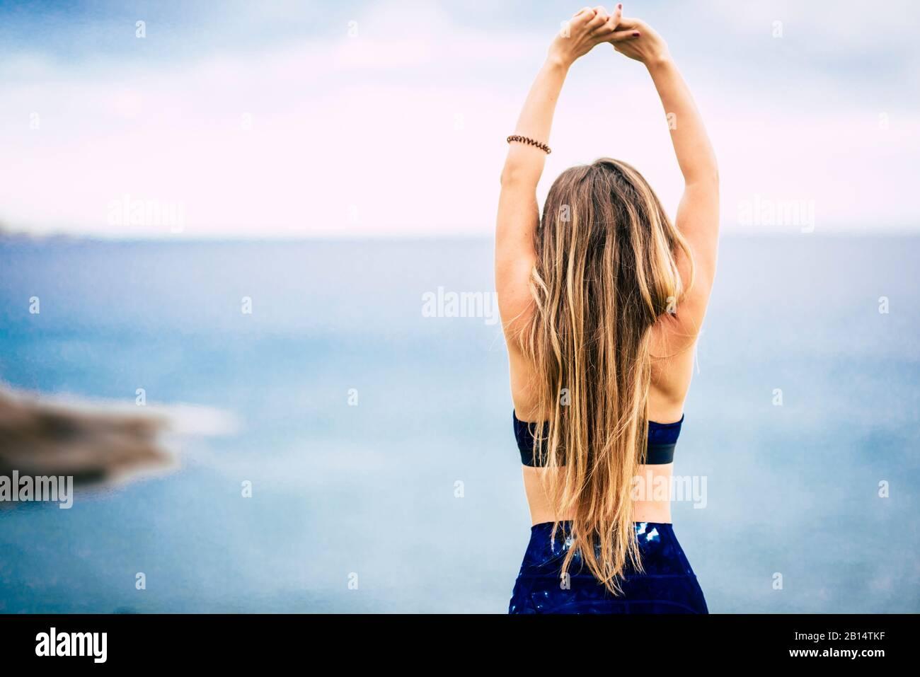 Mode de vie sain concept de personnes avec belle fille blonde de cheveux belle vue de l'arrière faire quelques étirements devant l'océan vue extérieur - la coupe wom Banque D'Images