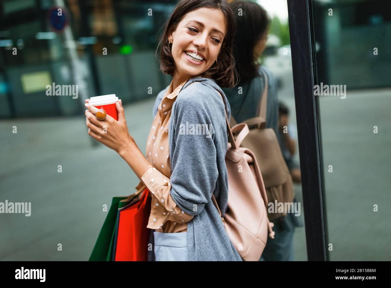 Une jeune femme heureuse à boire du café et à marcher avec des sacs après avoir fait du shopping en ville. Banque D'Images