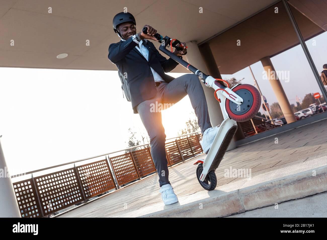 Homme d'affaires souriant avec scooter de poussée au coucher du soleil Banque D'Images