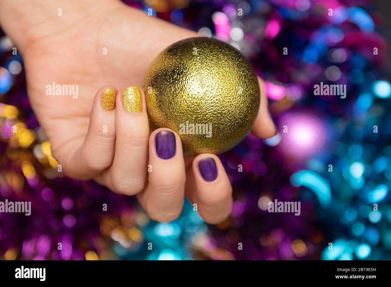 Belle main féminine avec motif clou de noël violet. Banque D'Images