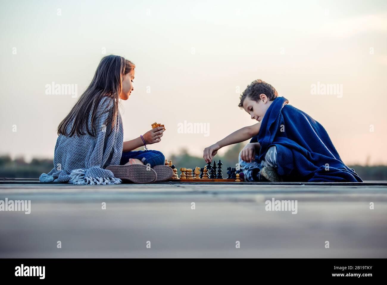 Deux jeunes petits amis mignons, un garçon et une fille qui s'amusent en jouant aux échecs assis près du lac le soir. Les enfants jouent. Amitié. Banque D'Images