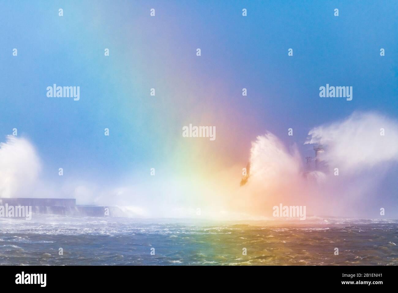 Vagues qui frappent le phare de la digue Carnot avec un arc-en-ciel créé par réflexion de lumière sur les vagues, pendant la tempête Ciara, Boulogne sur mer, Banque D'Images