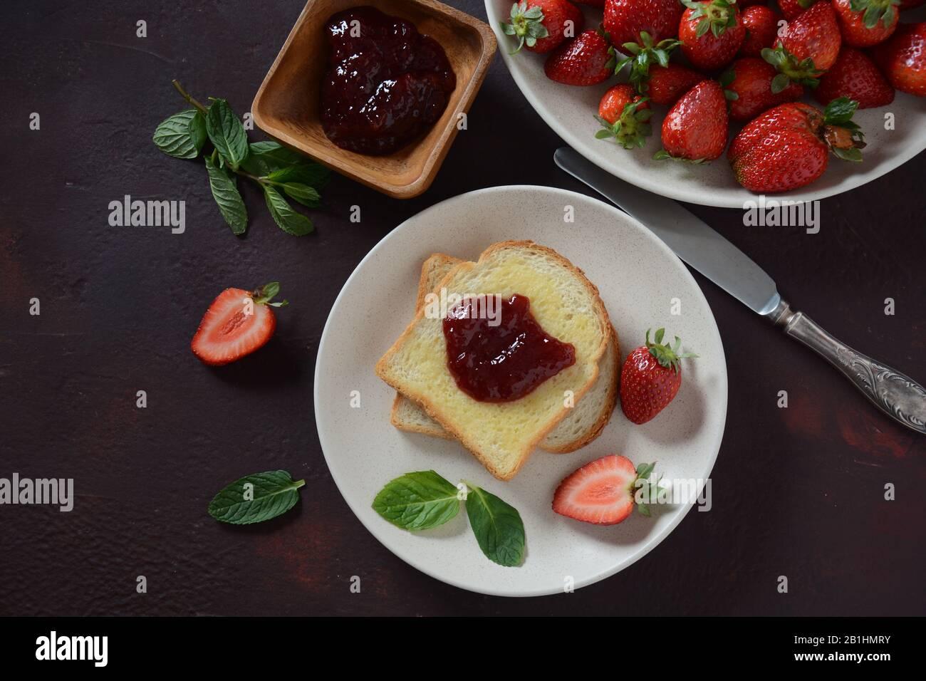 Toasts avec confiture de fraises pour le petit déjeuner, style rustique Banque D'Images