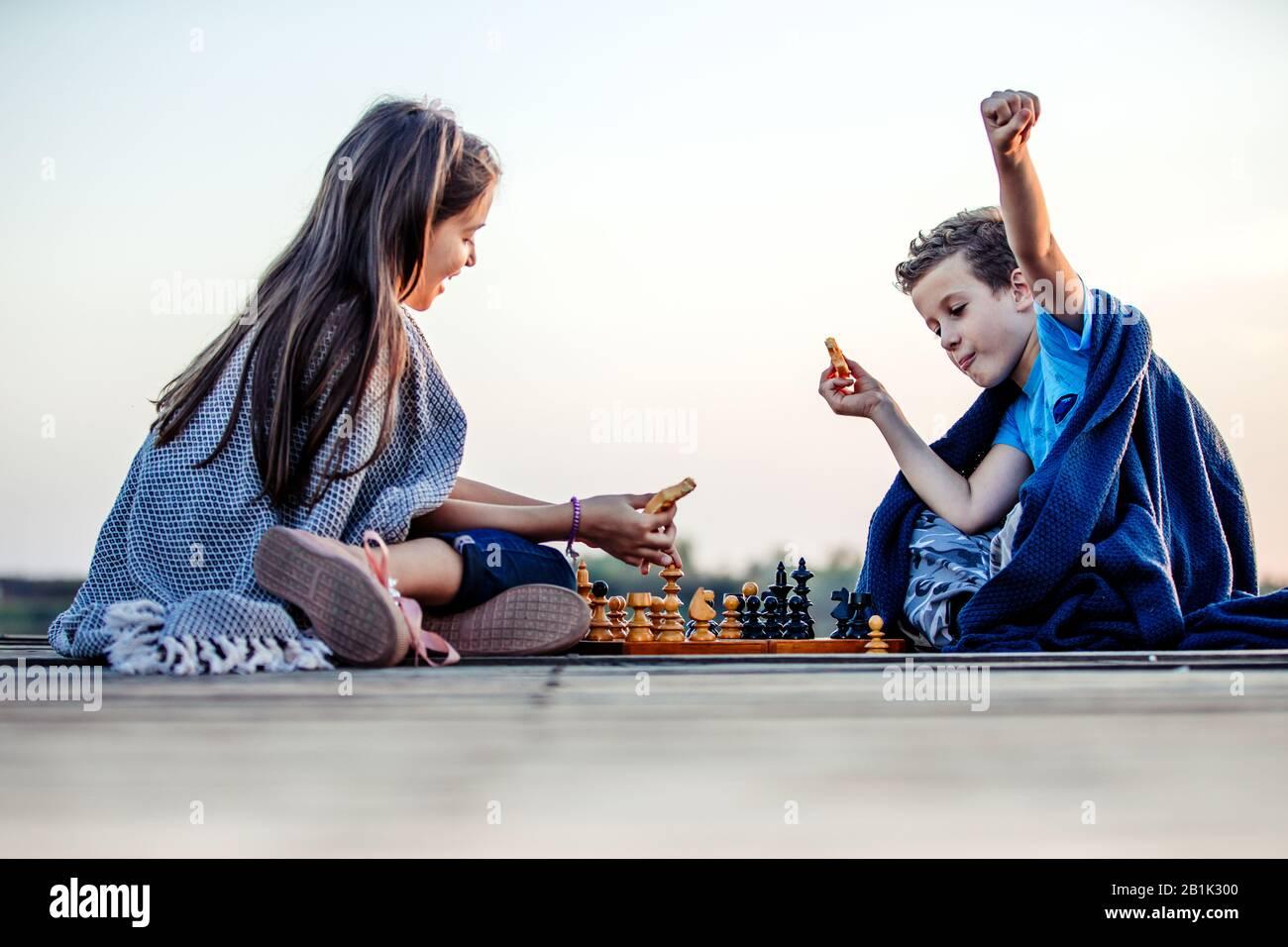 Deux jeunes petits amis mignons, un garçon et une fille qui s'amusent en jouant aux échecs assis près du lac le soir. Les enfants jouent.geste gagnant. Ami Banque D'Images