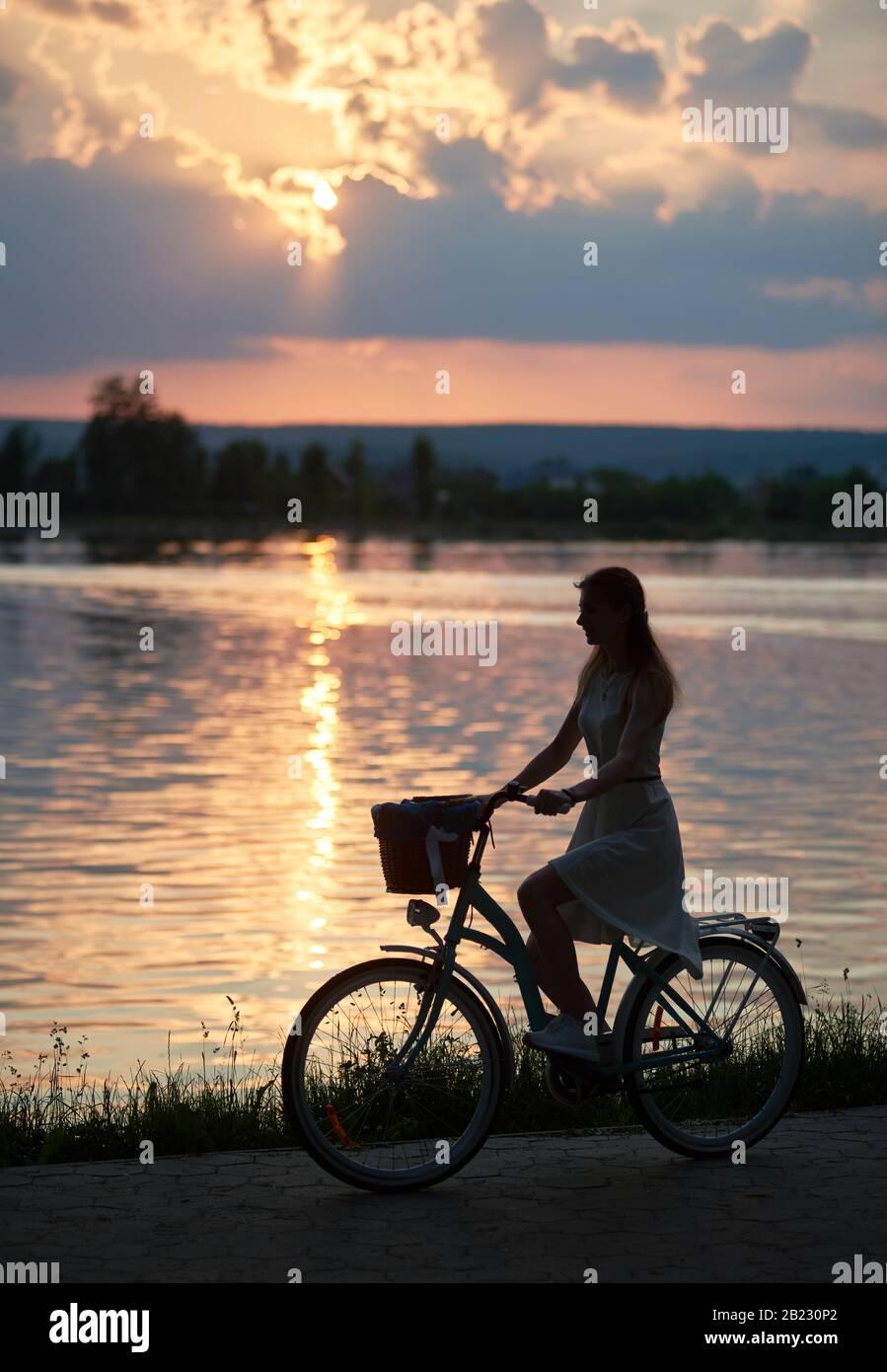 Silhouette d'une jolie fille qui monte un vélo le long du lac au beau coucher du soleil, horizon mauve et chemin du soleil sur l'eau, moments paisibles, espace de copie Banque D'Images