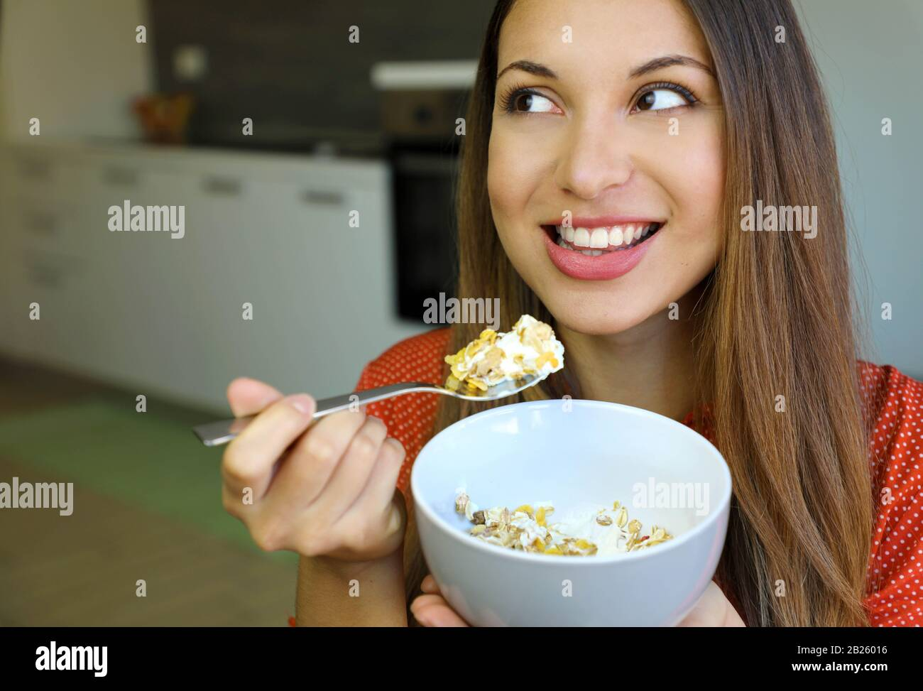 Gros plan sur la belle jeune femme mangeant des yaourts skyr avec des céréales muesli fruits à la maison, regardant sur le côté, se concentrer sur les yeux modèles, image intérieure. H Banque D'Images