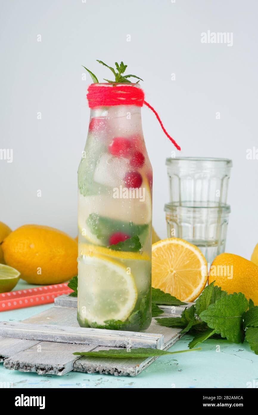 Boisson rafraîchissante de l'été avec de la limonade citron, canneberge, feuilles de menthe, la chaux dans une bouteille en verre, à côté les ingrédients pour faire un cocktail. Banque D'Images