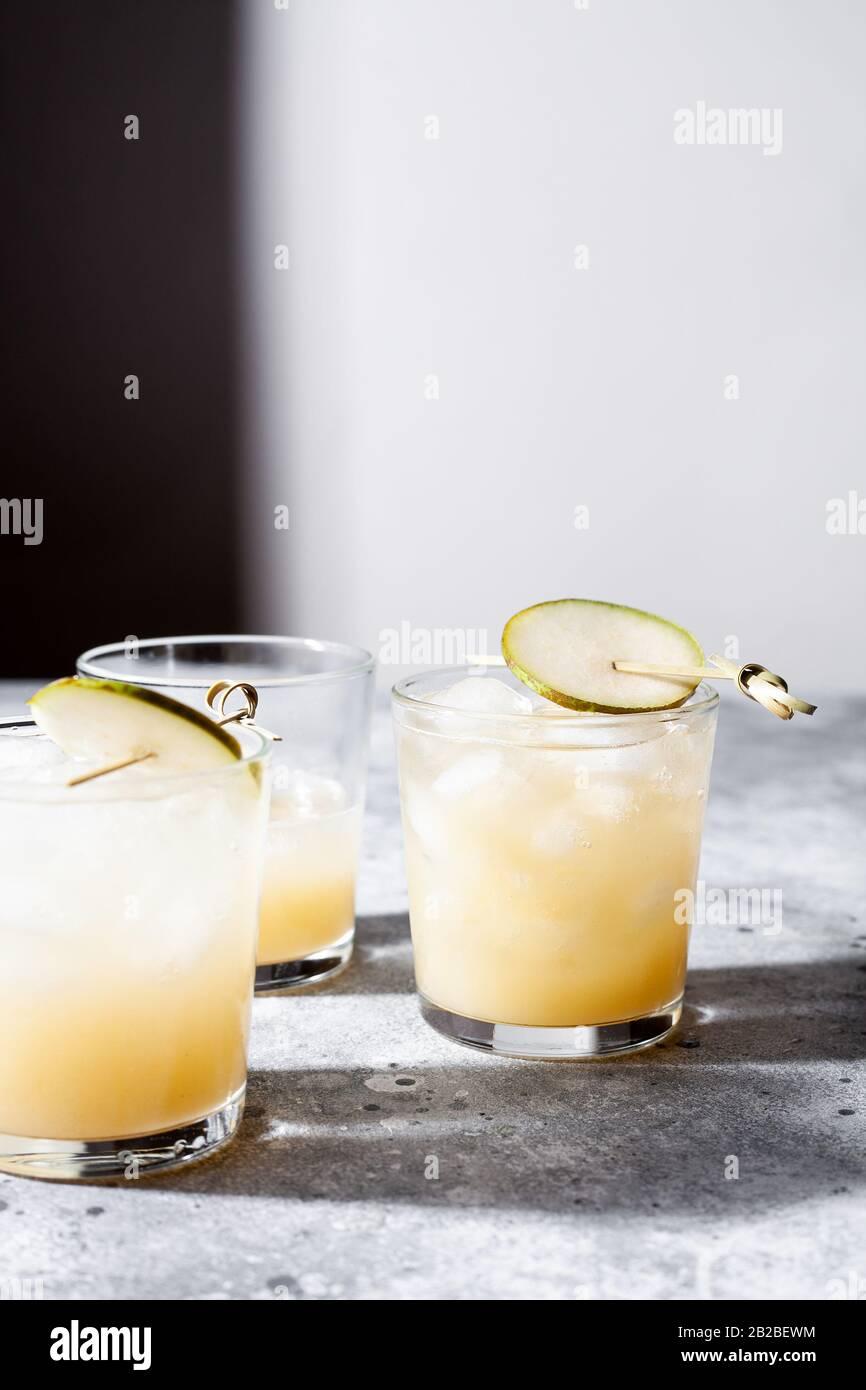 Un petit verre de mocktail ou de cocktail rafraîchissant à base de soda de poire sur fond de béton gris. Boisson estivale sans alcool. Mise au point sélective Banque D'Images