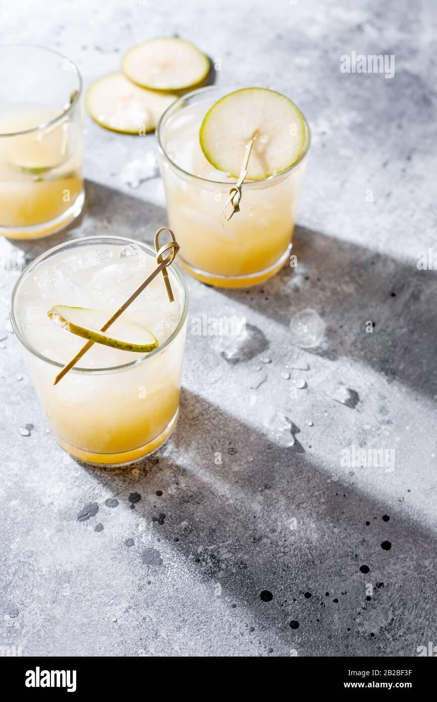 Cocktail de poire froide ou queue de bœuf avec purée de soda et de poire et tranches de fruits en verre court sur fond gris avec ombre. Boisson rafraîchissante en été Banque D'Images