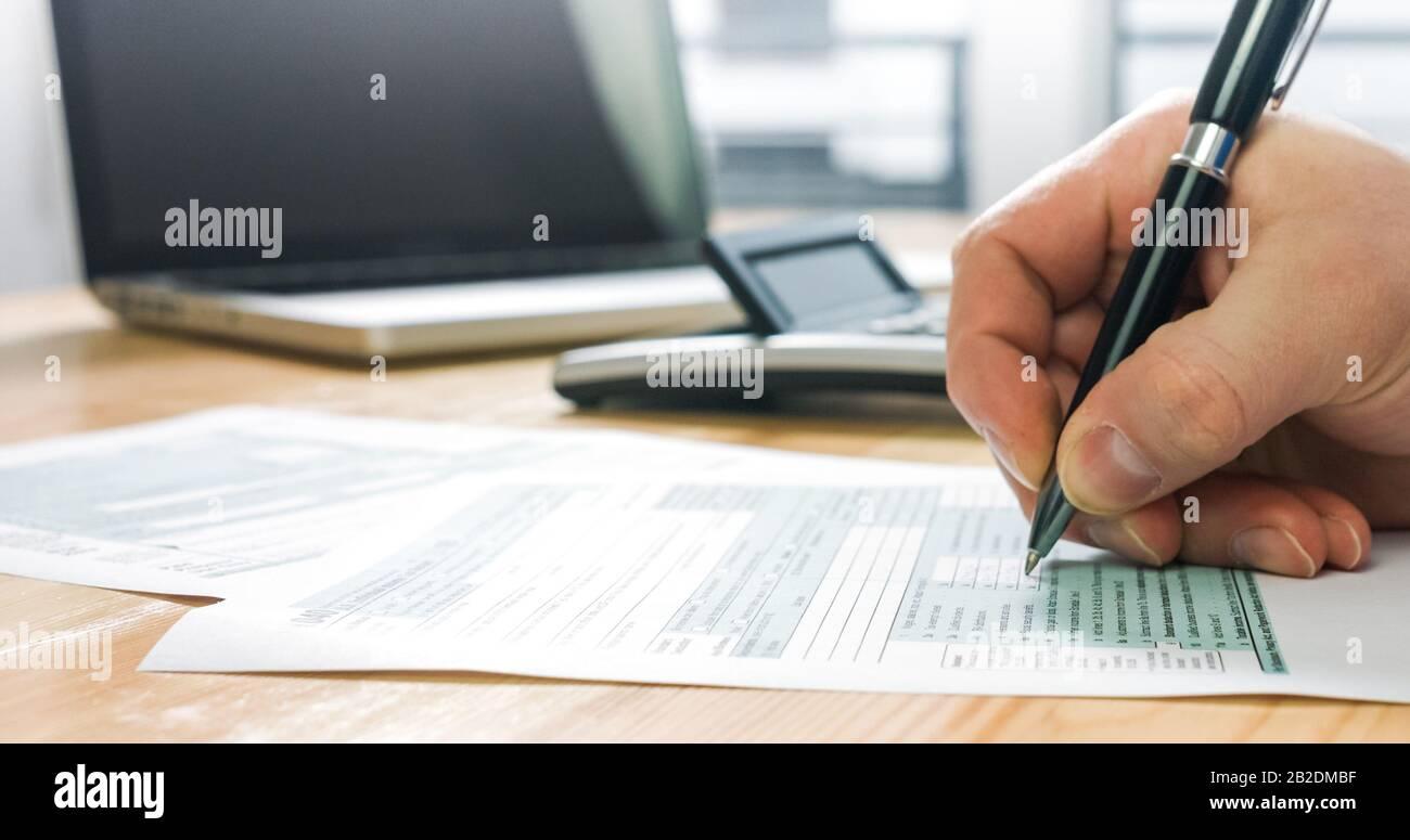 Gros plan du formulaire d'impôt américain 1040 et calcul et remplissage manuel du papier de rapport avec un ordinateur portable au bureau. Banque D'Images