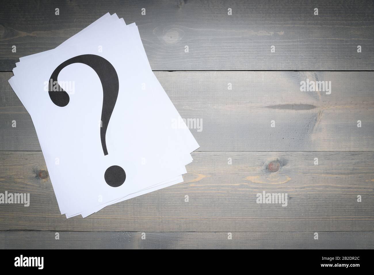 Pile de points d'interrogation imprimée sur du papier blanc sur fond gris Banque D'Images