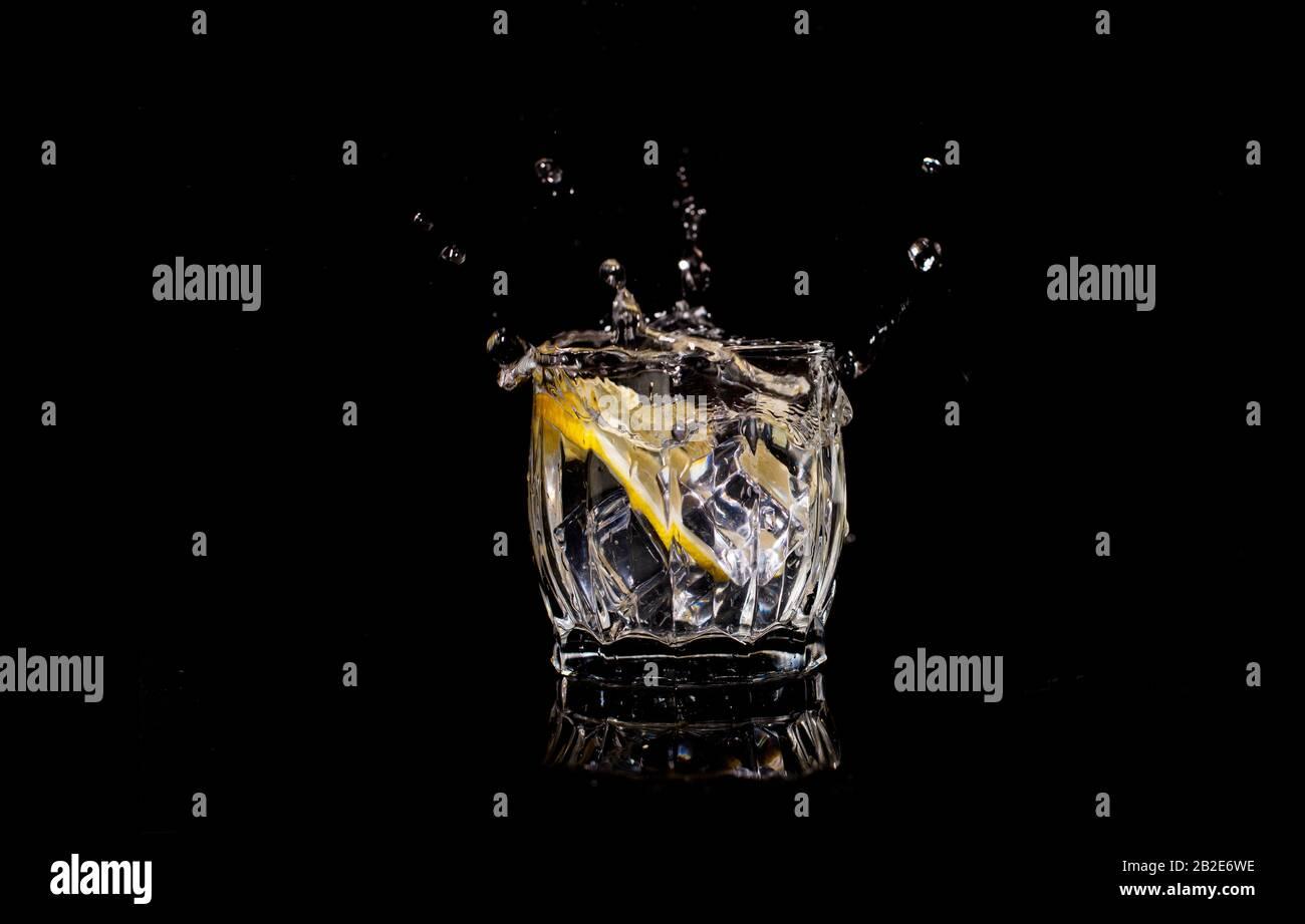 l'eau d'aqua avec du soda de citron déborde lorsque la glace est projetée avec des gouttes sur un backgroun noir Banque D'Images