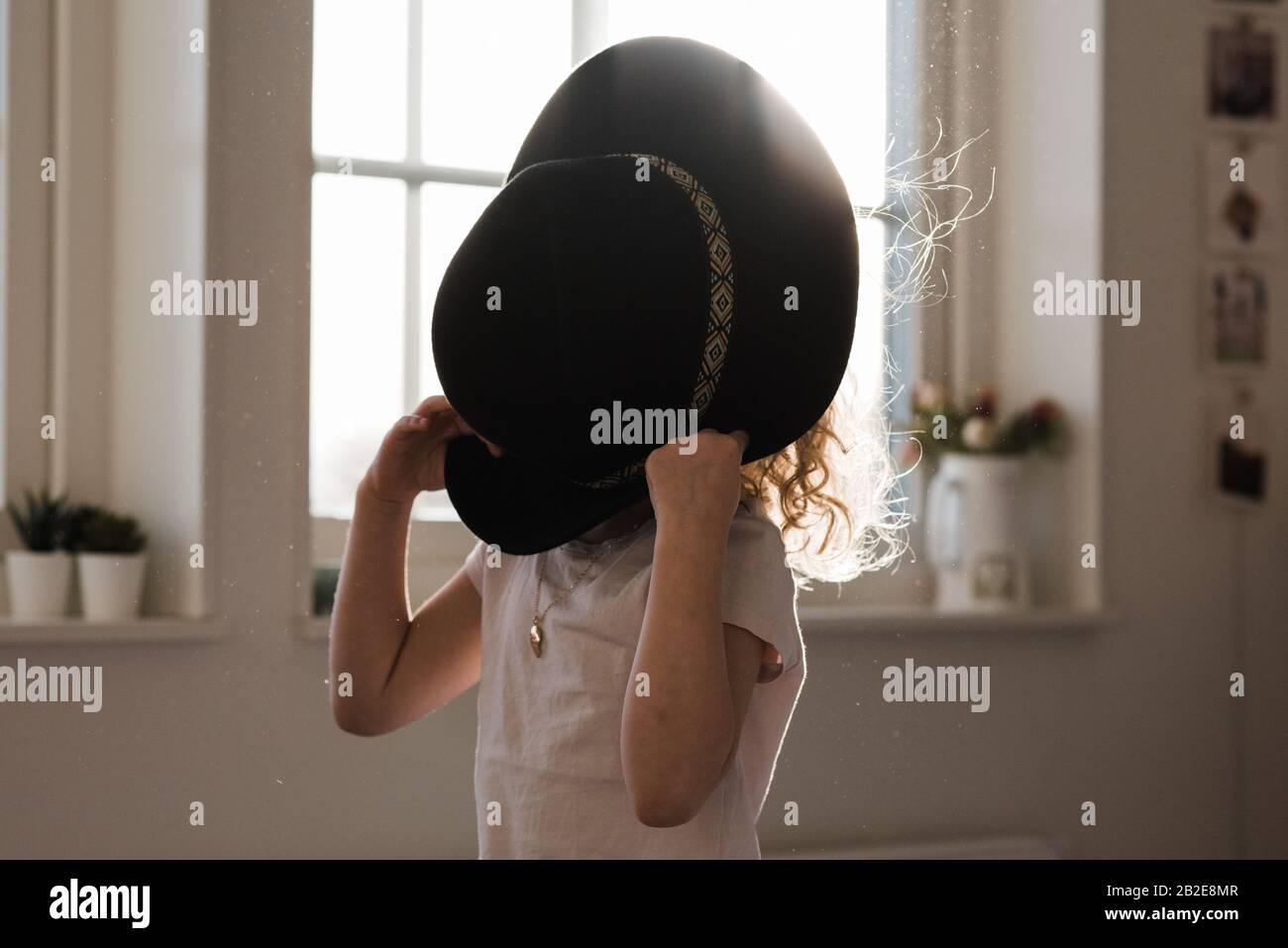 portrait d'une jeune fille jouant avec un chapeau couvrant son visage Banque D'Images