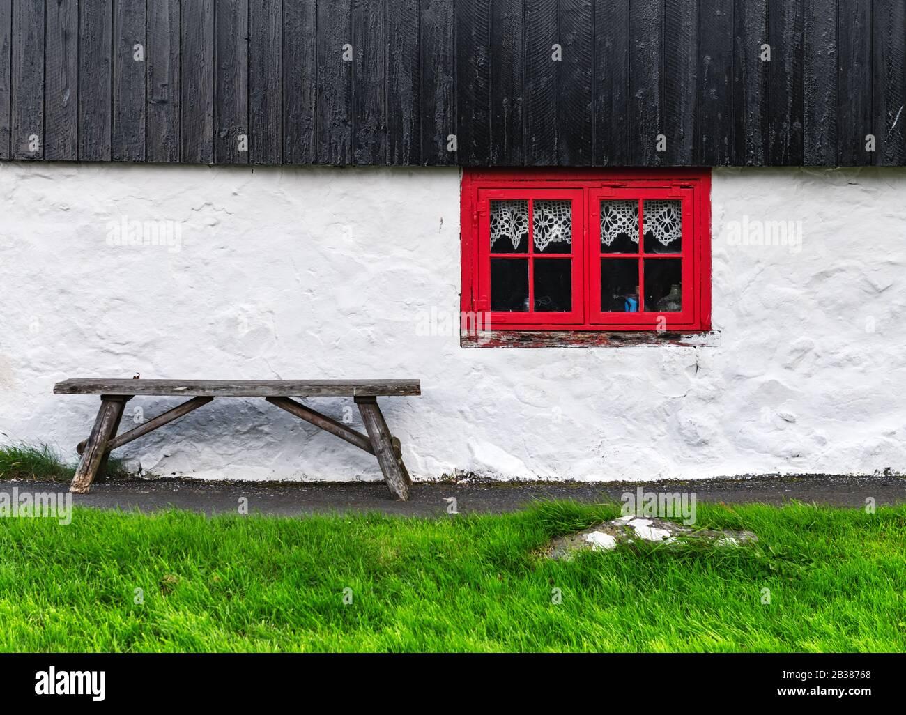 Mur de maison blanc avec fenêtre rouge sur la vieille maison faroese. Banc en bois sur l'herbe verte. Îles Féroé, Danemark Banque D'Images