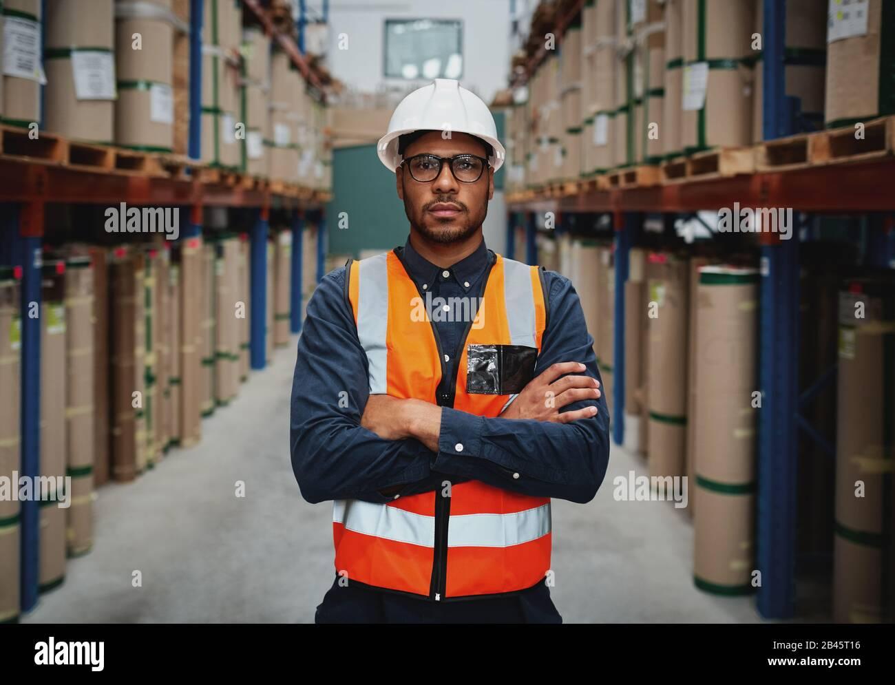 Jeune Manager confiant avec bras croisé portant un gilet orange et un casque blanc dans l'unité de fabrication regardant la caméra Banque D'Images
