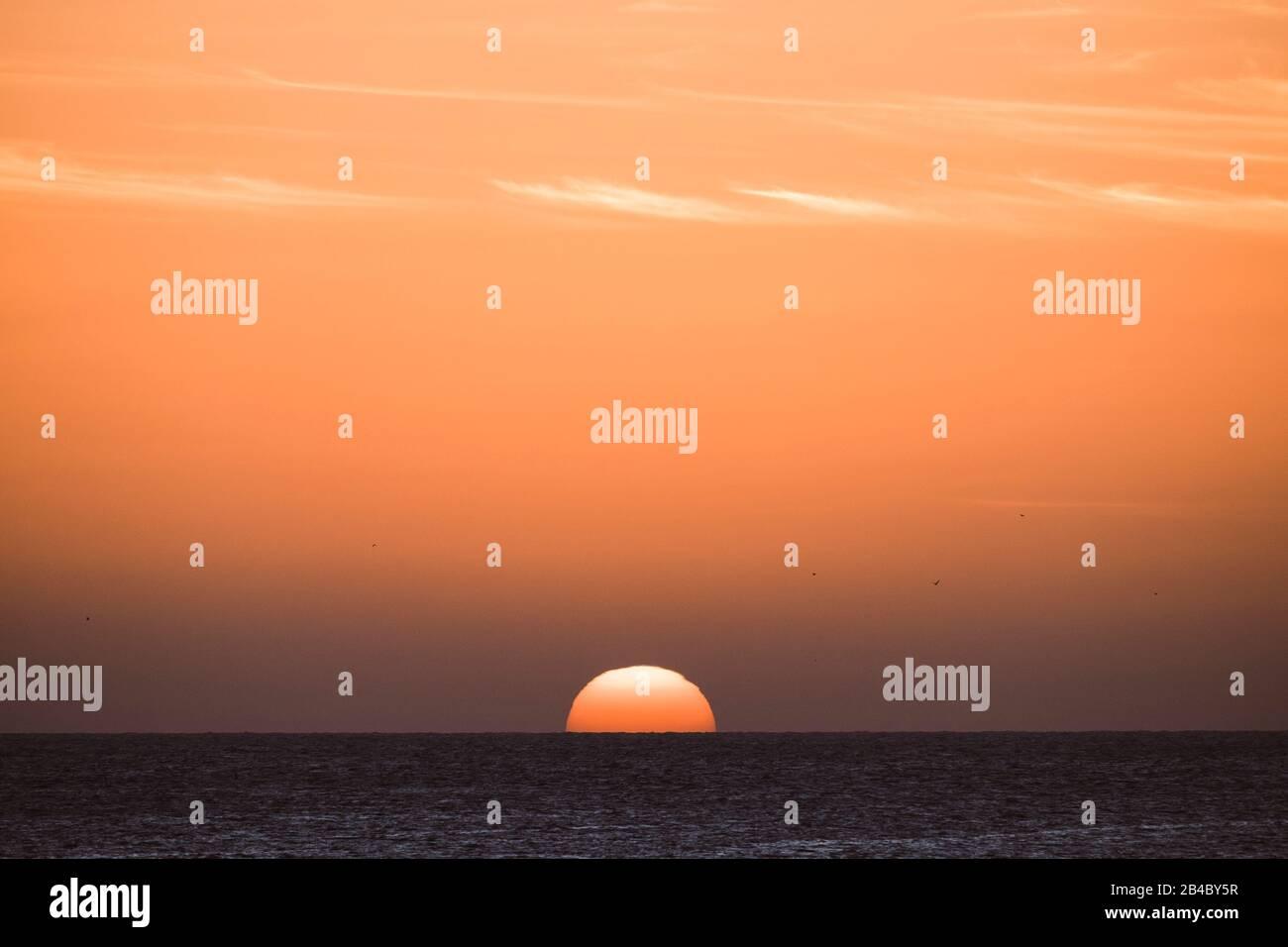 Coucher de soleil tropical classique ou lever de soleil sur l'horizon de la mer avec le soleil et l'eau se touchant ensemble - ciel orange chaud en arrière-plan - destination voyage paradis vacances concept Banque D'Images
