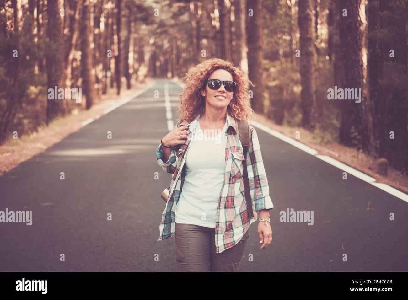 Joyeuses et joyeuses femmes voyagent gratuitement les gens qui marchent au milieu d'une longue route avec forêt et arbres autour - concept de voyage pittoresque - belle cacacasien curieusement femme profitant de l'activité de loisirs en plein air Banque D'Images