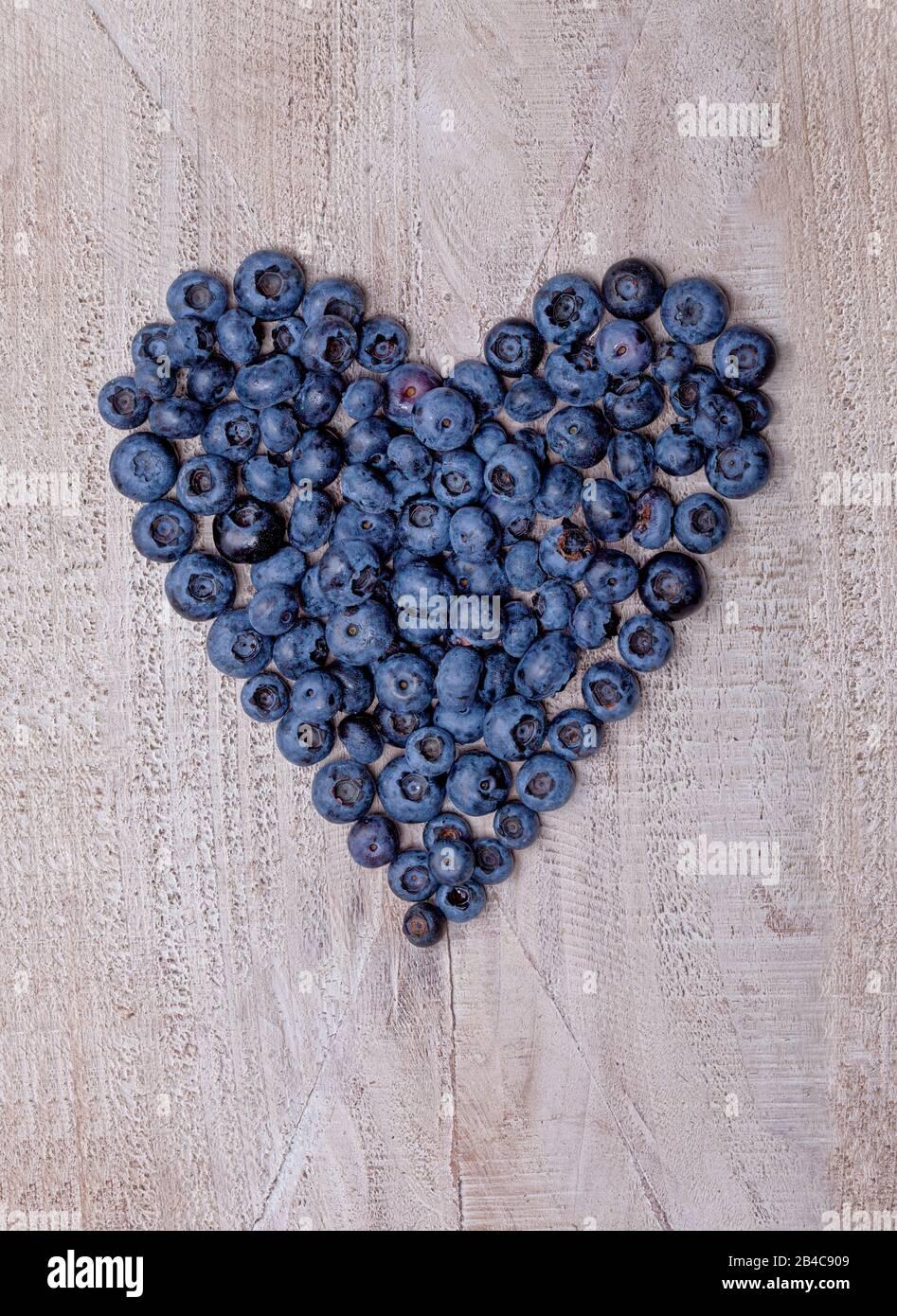 Coeur bleuets façonné sur plaque en bois Banque D'Images