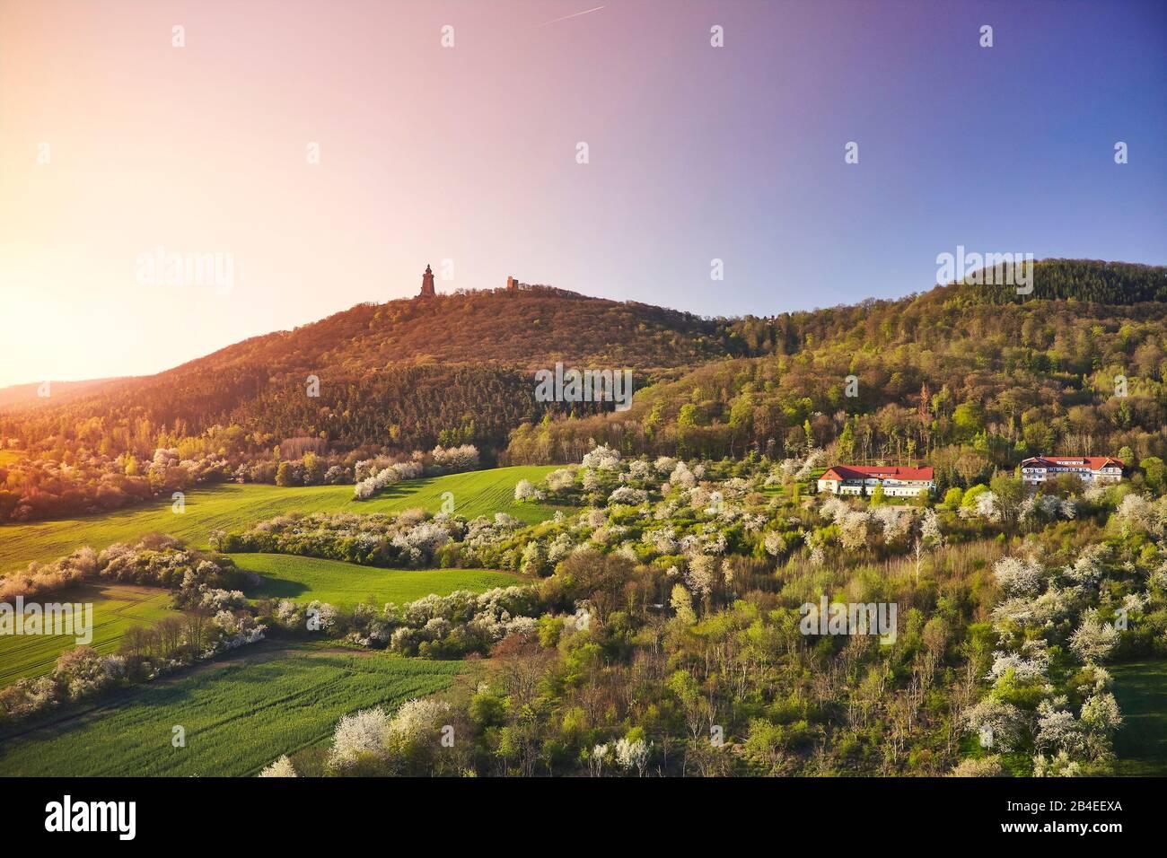 Allemagne, Thuringe, frontière avec Saxe-Anhalt, vergers en fleurs, collines avec le monument Kyffhäuser, troisième monument allemand, soleil radiant du matin Banque D'Images