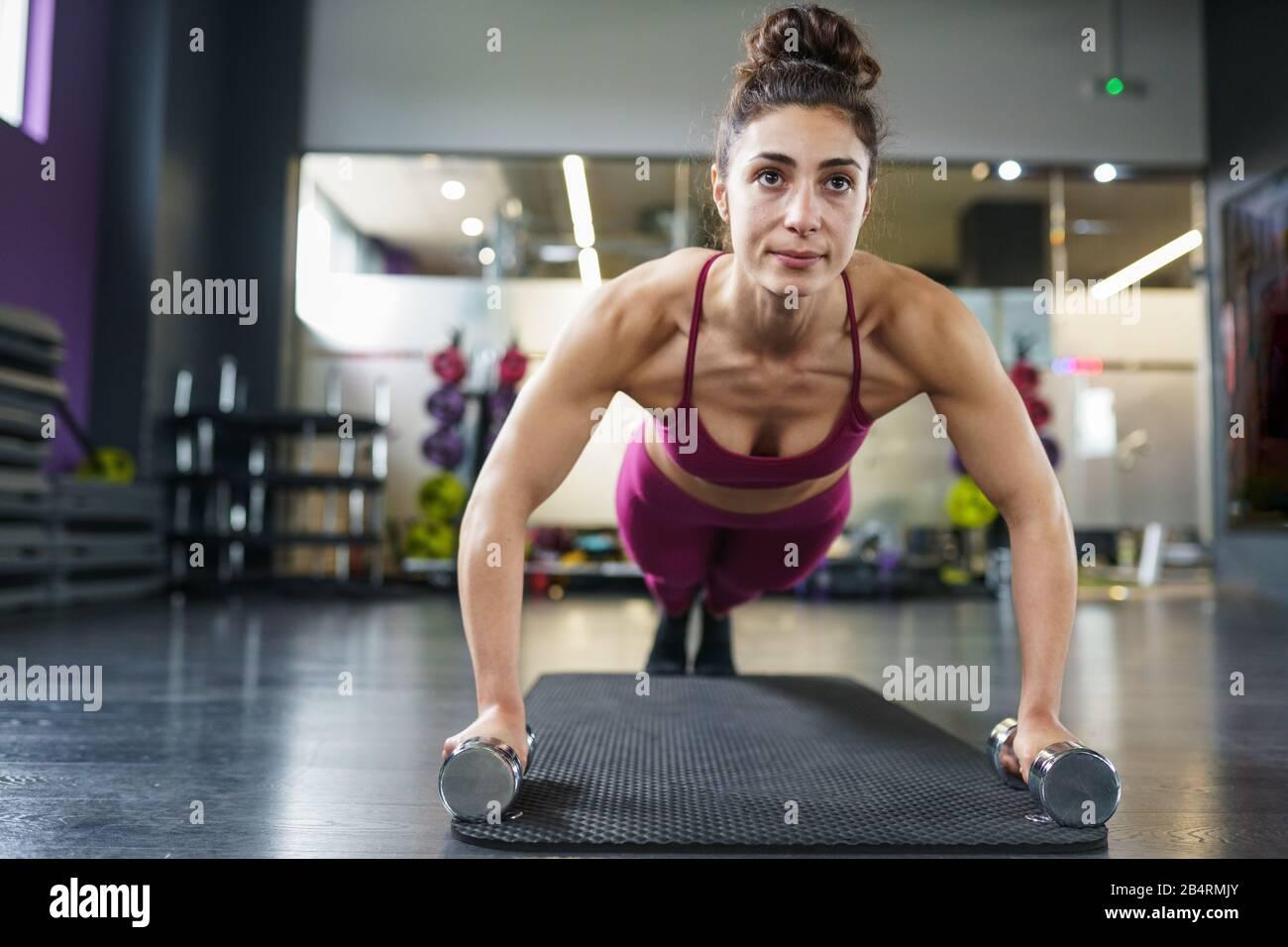 Woman doing push-ups exercice avec haltère dans un entraînement de fitness Banque D'Images