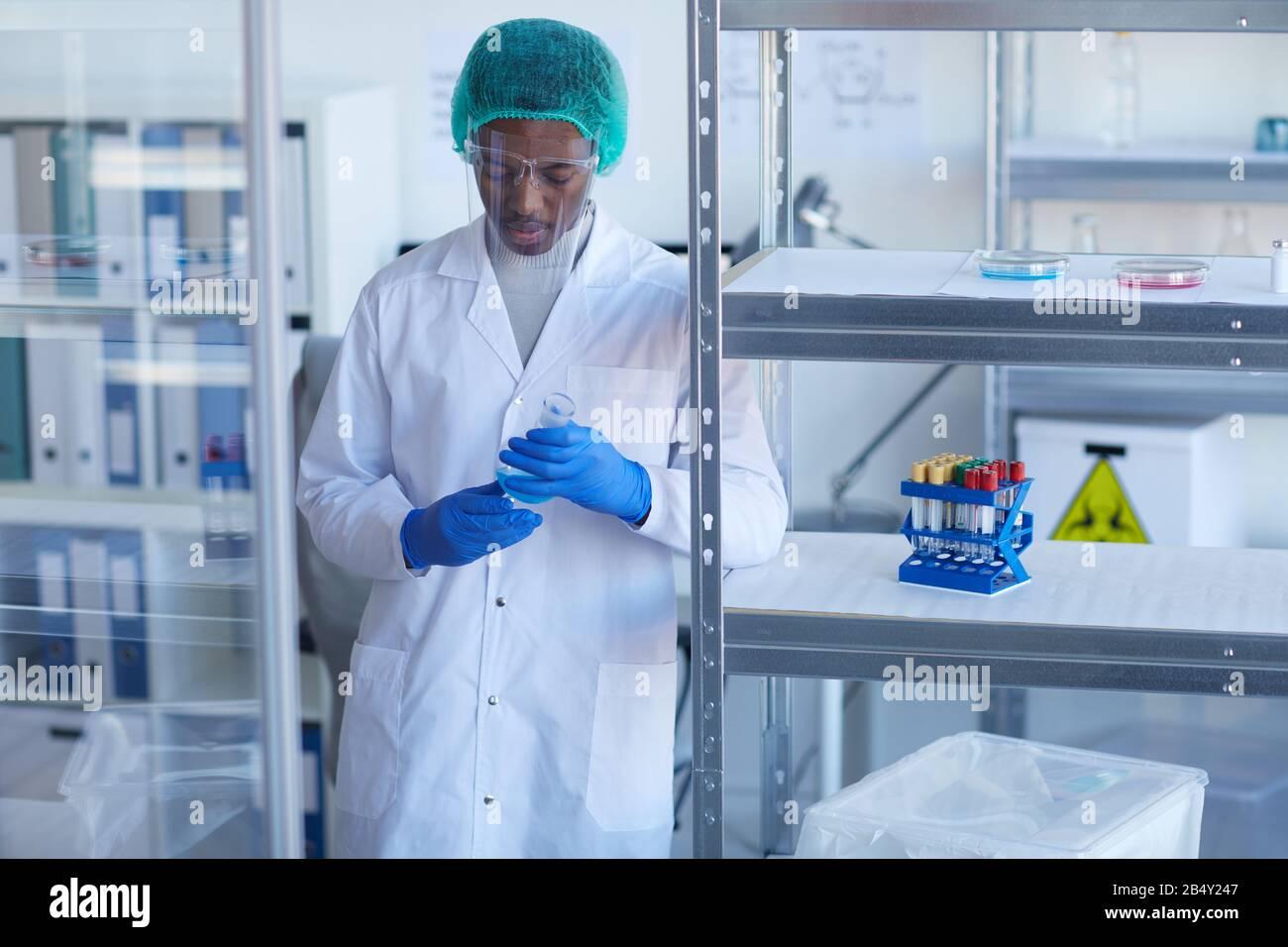 Portrait moyen horizontal d'un scientifique afro-américain en uniforme de protection travaillant en laboratoire Banque D'Images