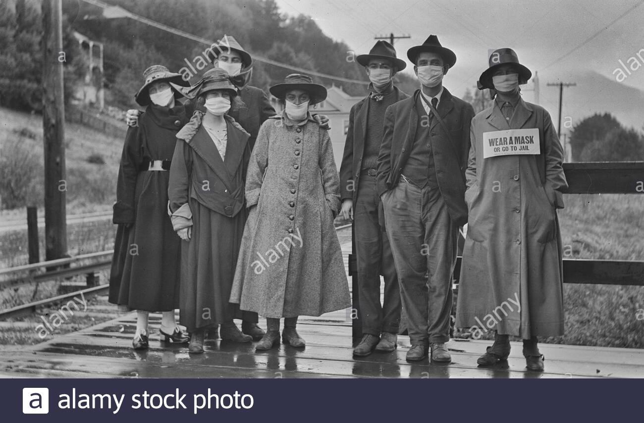 """Un groupe de personnes debout à l'extérieur portant des masques sur leurs bouches. C'était probablement durant l'épidémie de grippe espagnole de 1918. Une des femmes a un signe devant sa lecture """"Porter un masque ou aller en prison"""". Banque D'Images"""