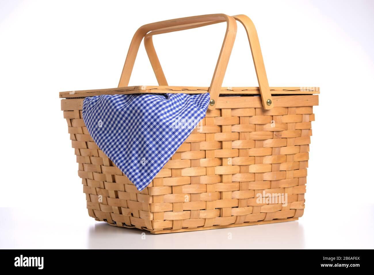 Panier pique-nique en osier sur fond blanc avec nappe Vichy bleue Banque D'Images