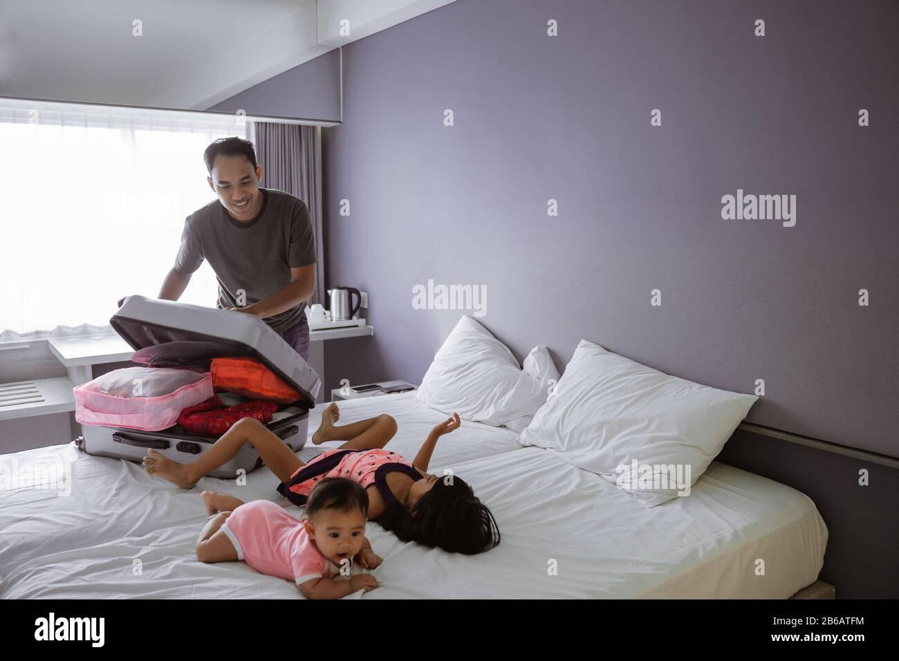 le père prépare la valise quand ses deux enfants jouent sur le lit dans la chambre Banque D'Images
