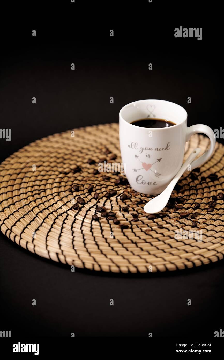 Tasse en céramique blanche avec les mots « tout ce dont vous avez besoin est amour » plein de café noir sur une table en bois, et grains de café Banque D'Images