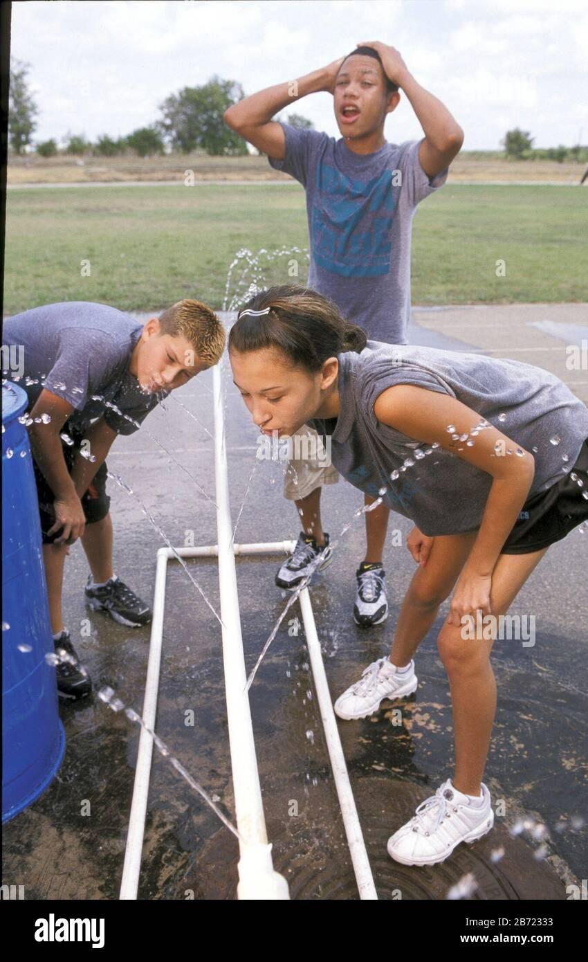 Pflugerville, Texas: Les enfants de l'école moyenne boivent de l'eau après s'exercer une journée chaude. ©Bob Daemmrich Banque D'Images