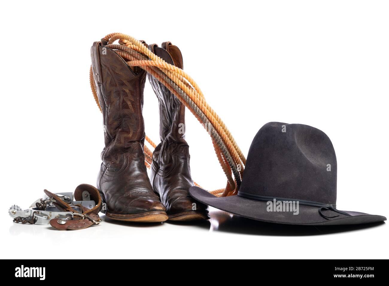 Bottes occidentales et une corde de tour ou de lariat et des espions et un chapeau de cowboy sur un fond blanc Banque D'Images