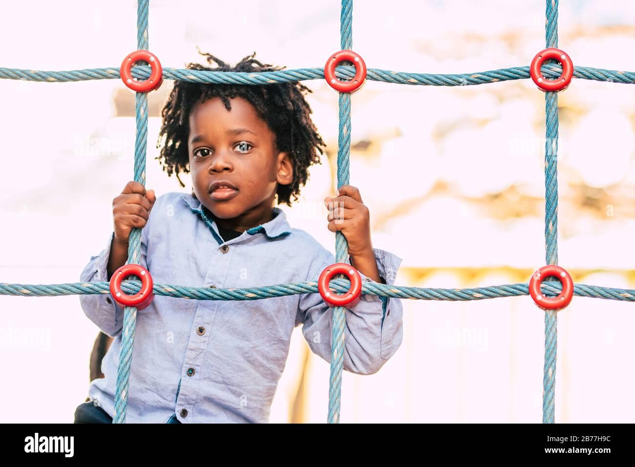Heureux et beau jeune enfant race noire africaine avec des cheveux alternatifs ethniques jouant dans un terrain de jeu avec des cordes colorées et s'amuser Banque D'Images