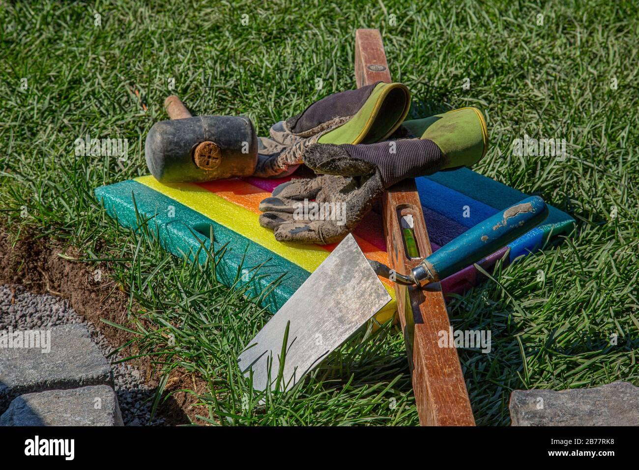 deux gants de travail, un maillet en caoutchouc, un niveau à bulle, une truelle et un tampon en mousse allongé dans l'herbe pendant une rupture en plaçant des pavés Banque D'Images