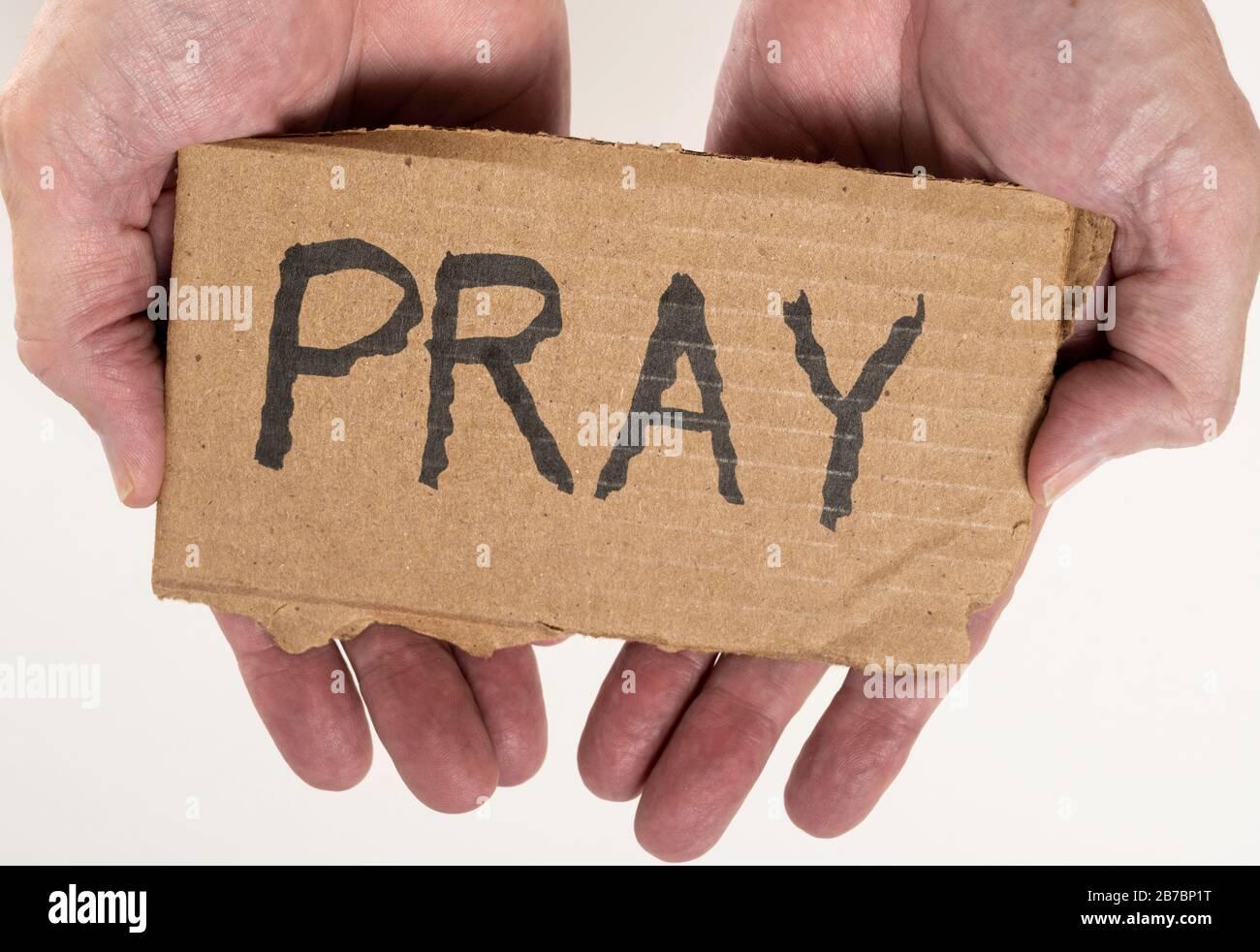 Carton signe avec PRIER écrit sur lui tenu dans la paume des mains Banque D'Images