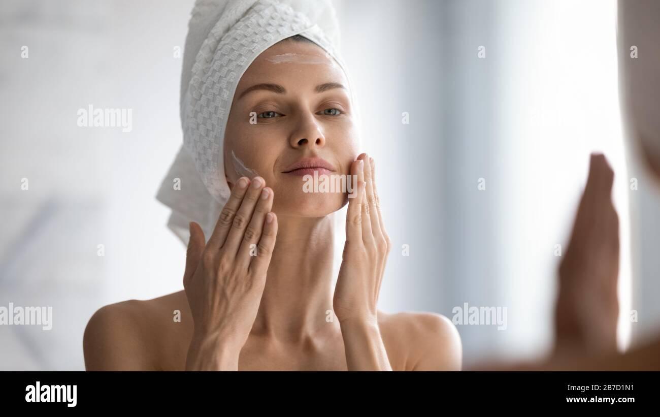 Jeune fille souriante enveloppée de lissage de serviette perfectionnant la peau. Banque D'Images