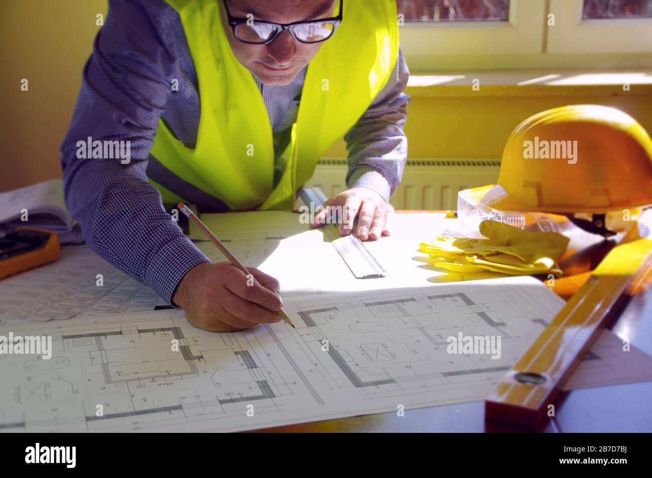 Responsable de la construction, entrepreneur, constructeur ou ingénieur sur le lieu de travail. Homme en train de travailler sur l'esquisse de construction. Architecture, ingénierie et concept industriel. Banque D'Images