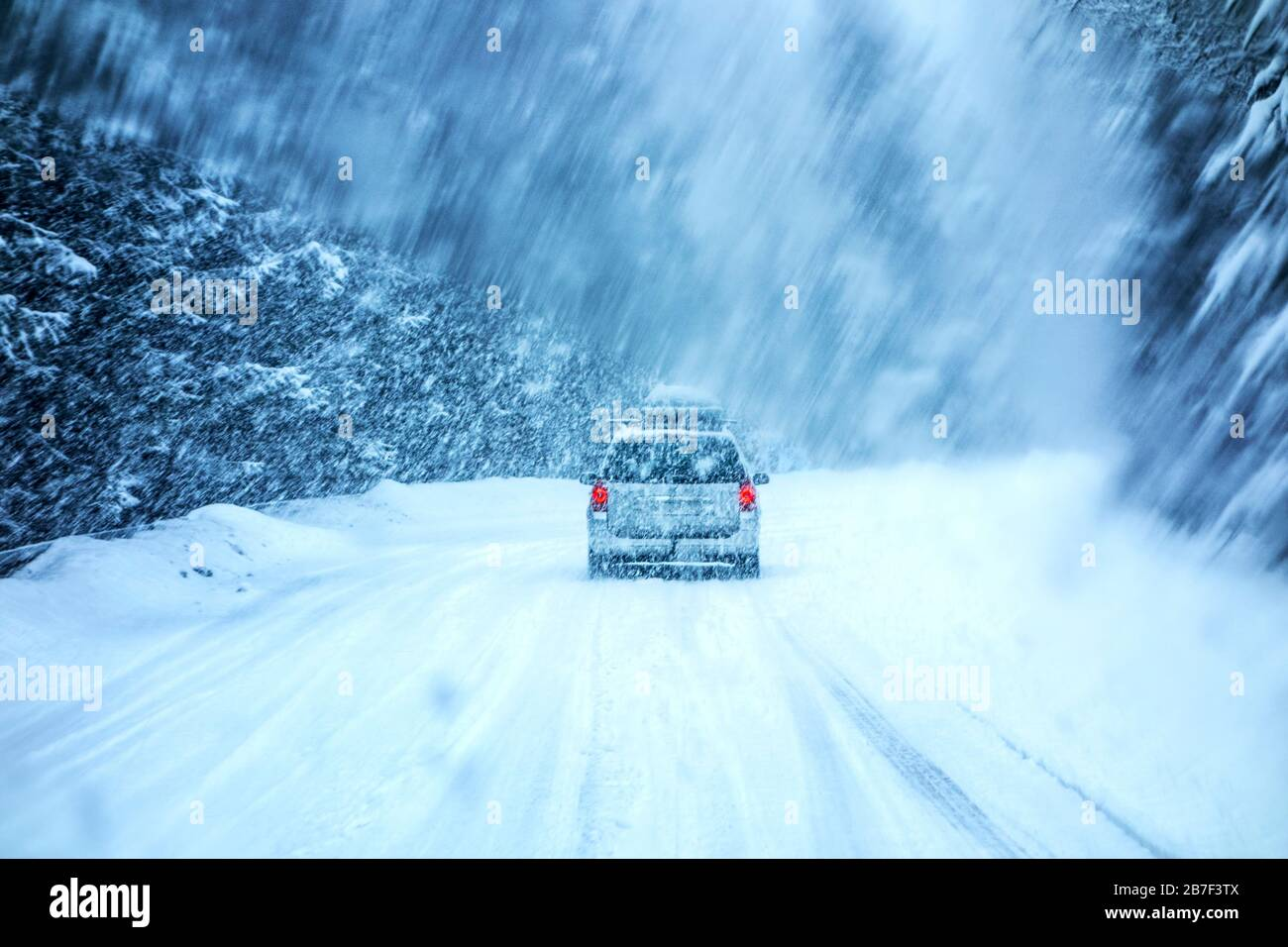 Conduite en voiture pendant la tempête de neige d'hiver à travers un pare-brise recouvert de flocons de neige flous. Banque D'Images
