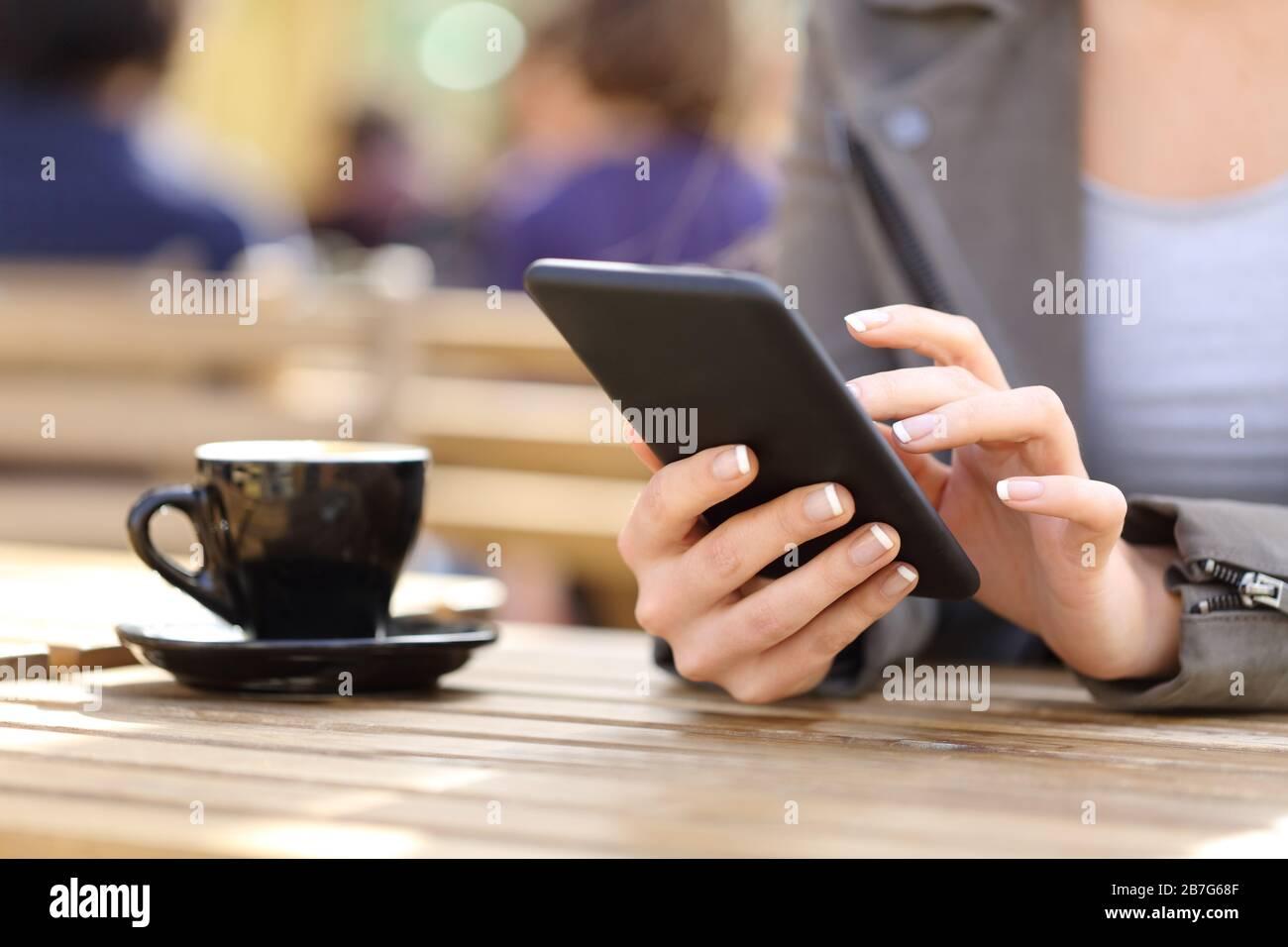 Gros plan sur les mains de la femme à l'aide de son téléphone portable sur une terrasse de café Banque D'Images