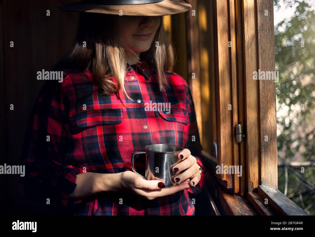 Femme en chemise à carreaux rouge holding tasse de thé avec de la vapeur dans le village house Banque D'Images