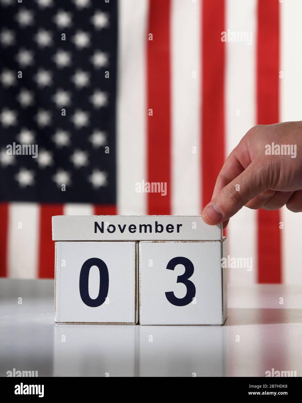 Une main sauva la date du 3 novembre 2020 pour l'élection présidentielle démocratique avec un drapeau américain dans le contexte d'un concept d'électeur. Banque D'Images
