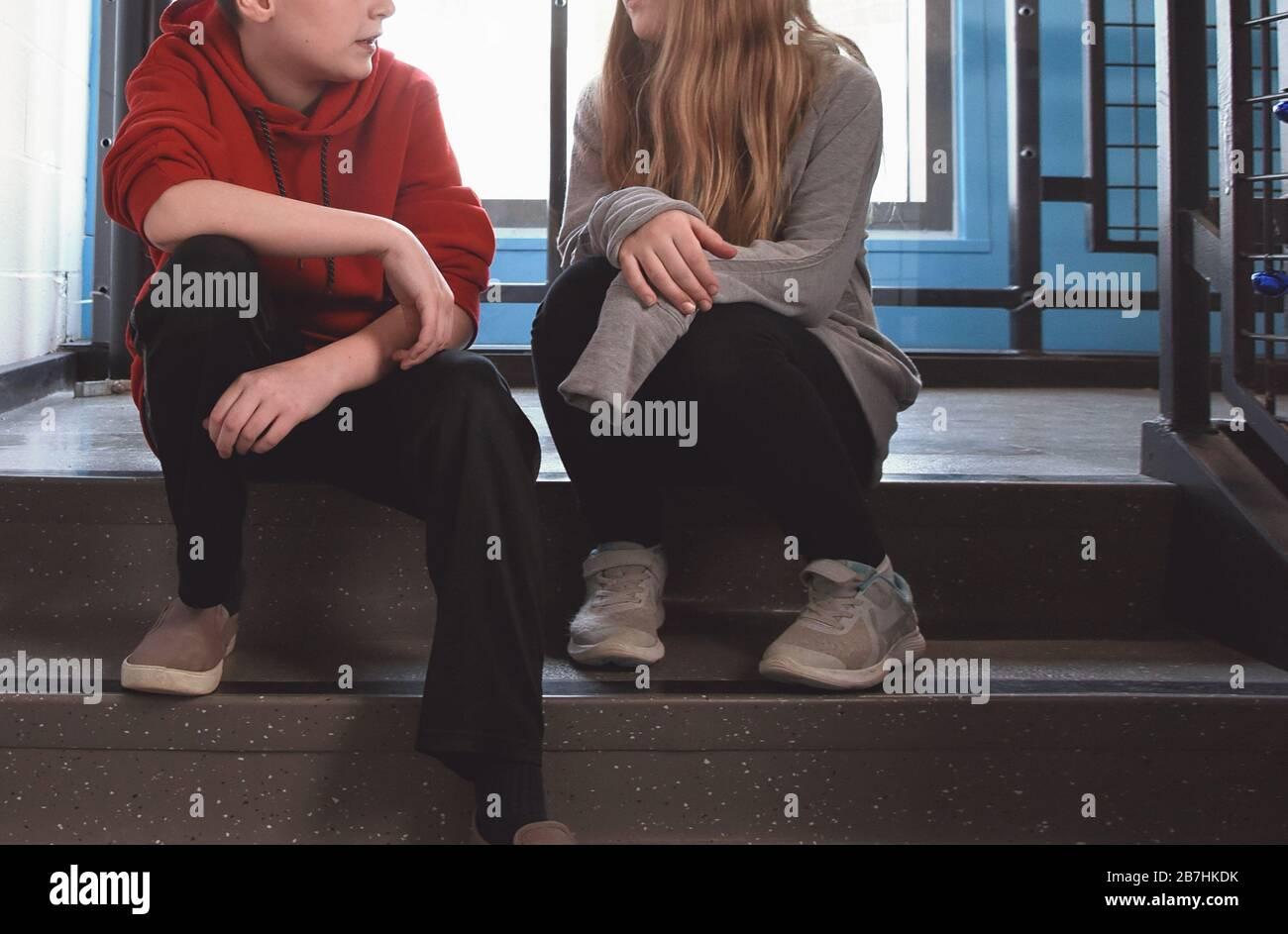 Un garçon et une jeune étudiante sont assis dans un couloir sur les escaliers pour parler d'un concept de communication avec les jeunes. Banque D'Images