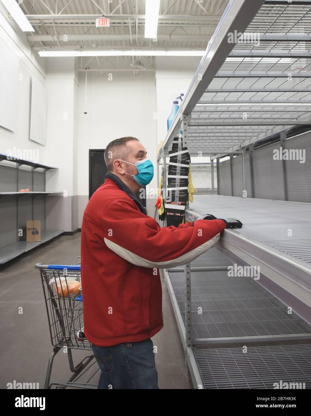 Un homme se tient dans une épicerie portant un masque antivirus en regardant le plateau vide pour un concept de pandémie de virus corona. Banque D'Images