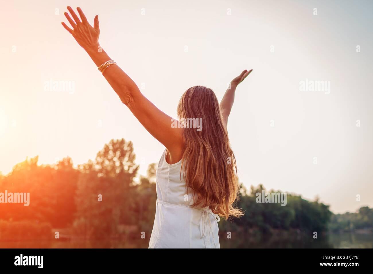 Femme d'âge moyen mûre profitant du coucher du soleil avec des bras élevés se sentant heureux dans le parc de printemps. Femme senior admire le paysage Banque D'Images