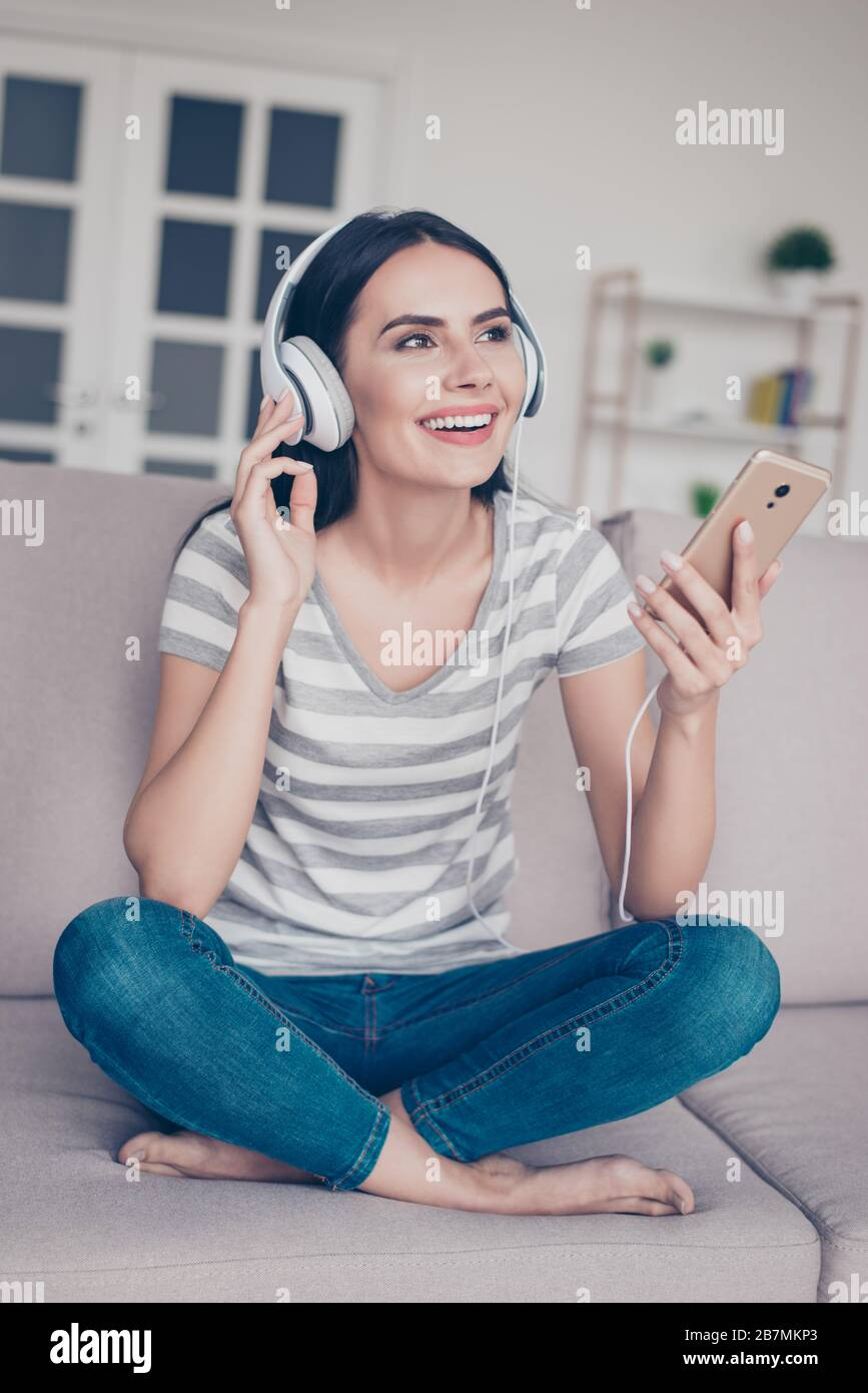 Photo verticale d'une jeune femme souriante excitée assise sur un canapé avec jambes croisées tenant smartphone et écoutant de la musique Banque D'Images