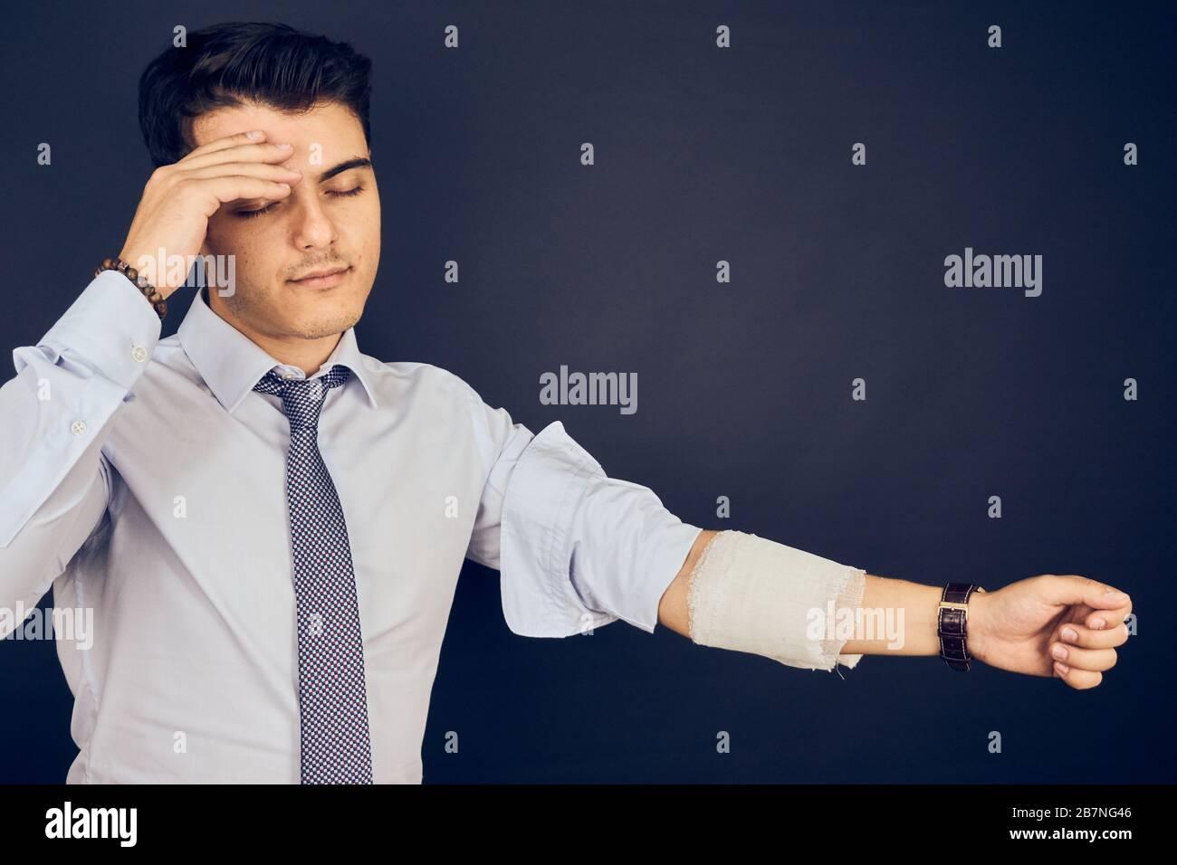 Jeune homme avec maux de tête et bandage sur la main Banque D'Images