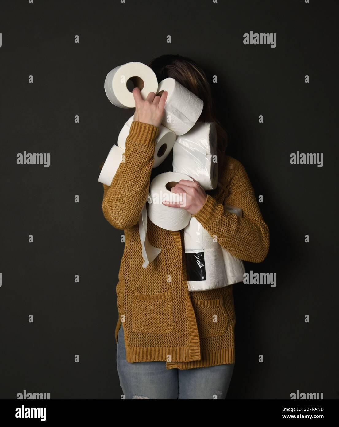Une femme tient une pile de fournitures de papier toilette pour un concept de demande des consommateurs concernant la pandémie du virus corona. Banque D'Images
