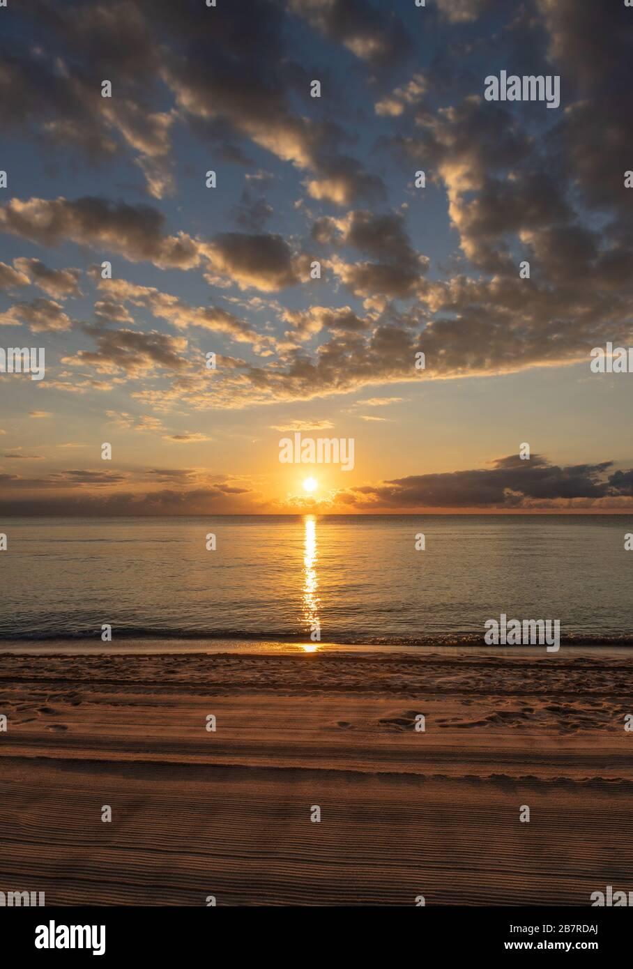 Magnifique lever de soleil près de la plage à Cancun, au Mexique, avec des reflets dorés sur la mer des Caraïbes. Banque D'Images